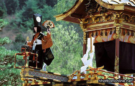 Những con búp bê biết biểu diễn được đặt trước một số kiệu rước trong lễ hội