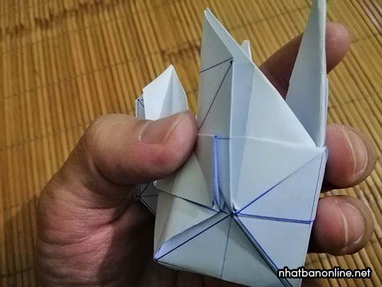 Kéo mép giấy nhô ra và nhét xuống dưới theo hình
